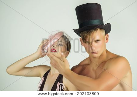 Fashion and style concept. Man or macho with muscles in black top hat. Couple in love posing on grey background. Fitness and beauty. Woman or girl wearing sexy lingerie and veil hat.