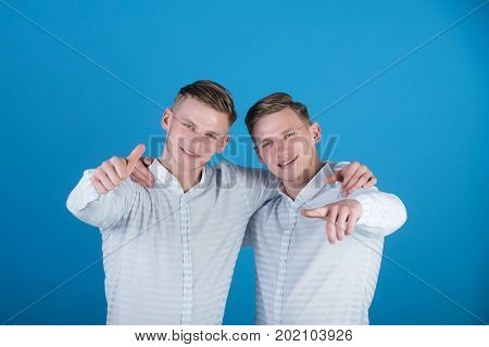 Models standing on blue background. Two brothers smiling and pointing fingers. Happy men hugging. Twins wearing striped shirts. Family brotherhood and friendship concept.