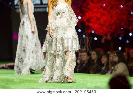 Sofia, Bulgaria - 21 March, 2017: A female model walks the runway in beautiful white dress during a Fashion Show. Fashion catwalk event showing new collection of clothes.
