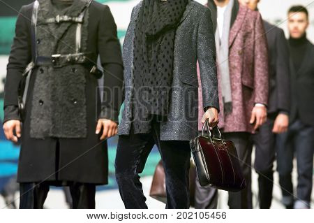 Sofia, Bulgaria - 23 March, 2017: Men models walk the runway during a Fashion Show. Fashion catwalk event showing new collection of clothes. Holding expensive brown bag.