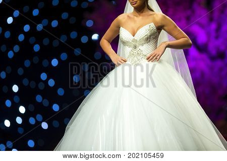 Sofia, Bulgaria - 23 March, 2017: A female model walks the runway in beautiful stylish white wedding dress during a Fashion Show. Fashion catwalk event showing new collection of clothes.