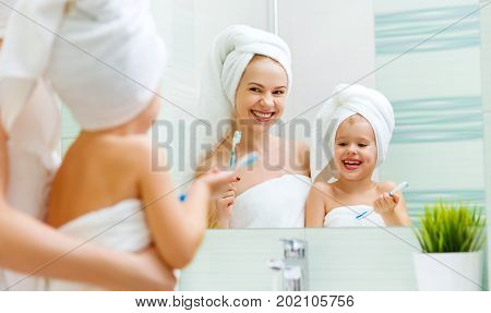 Mother and child daughter brush their teeth with a toothbrush in the bathroom