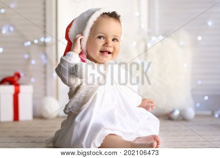 Cute little baby in Santa hat sitting on floor against blurred Christmas lights