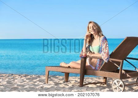 Beautiful young woman relaxing on sun lounger at sea resort
