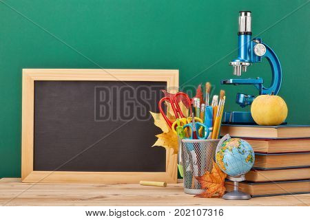 School background with stationery accessories.Books, globe, pencils and various office supplies  lying on the desk on a green background.