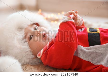 Happy cute baby in Santa suit with candy lying on knitted fabric