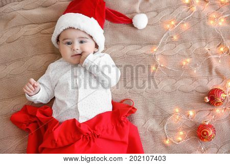 Cute little baby with Santa hat in red bag and Christmas lights on knitted fabric