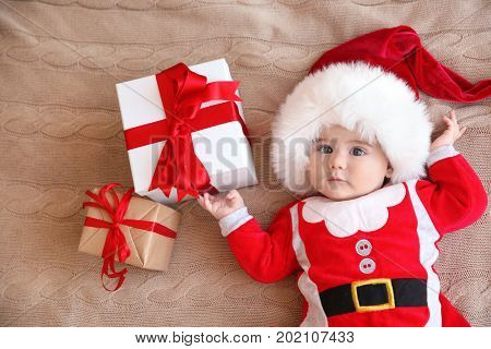 Happy cute baby in Santa suit with gift boxes lying on knitted fabric