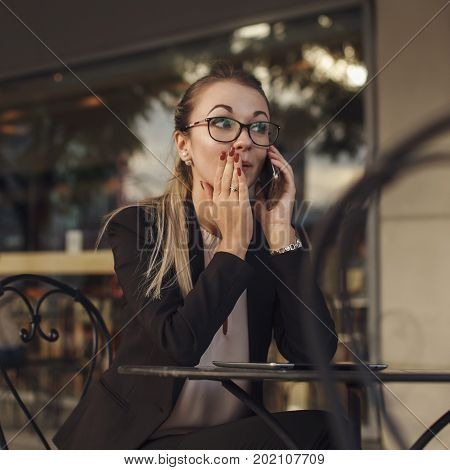 Business woman in suit with glasses telling a secret by the phone gossip rumor at work