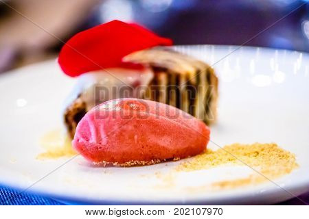 Strawberry Sorbet And A Roll Of Sponge Cake Lay On The Plate.