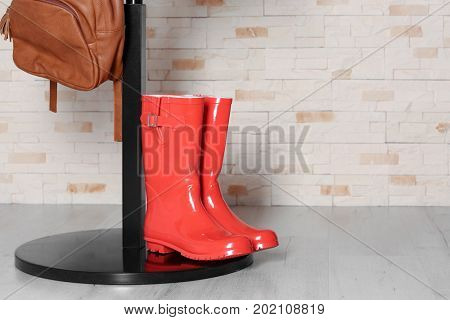 Red wellington boots and hall-stand near brick wall