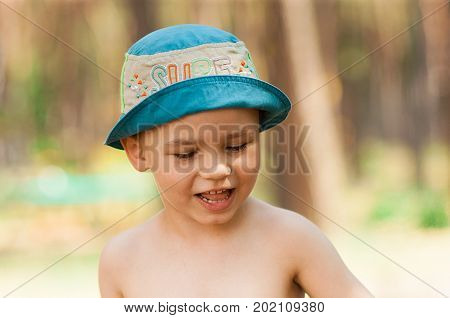 Outdoor close up portrait of little boy in a hat. Background, one person, child, 4-5 years old, summer day.