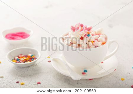 Pink unicorn hot chocolate with marshmallows and sprinkles