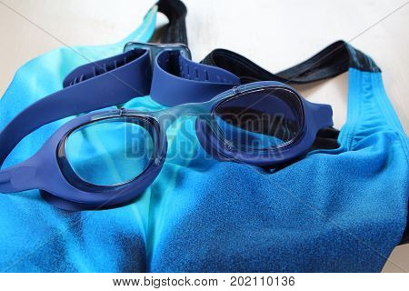 Blue swimming goggles and blue swimsuit for bathing in swimming pool
