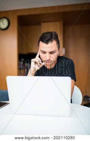 Man Sitting At Desk Working From Home On Laptop In The Morning