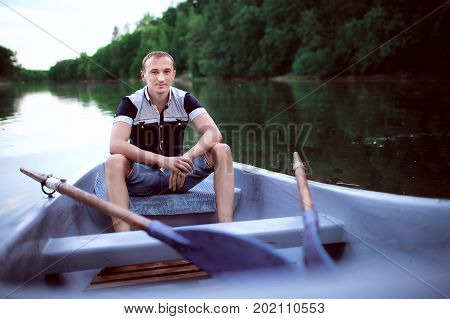young guy sits in the white boat, handsome teenager in light shorts and shirt looking on river, man enjoys outdoor recreation