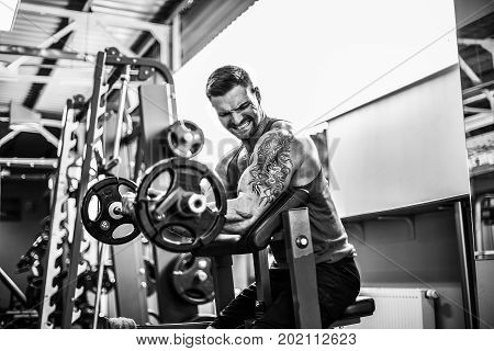 Bearded tattoed Man bodybuilder doing the set of a barbell exercise in a gym.