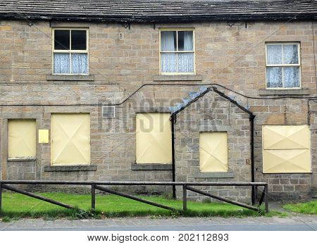 derelict abandoned terraced housing in england with boarded up windows