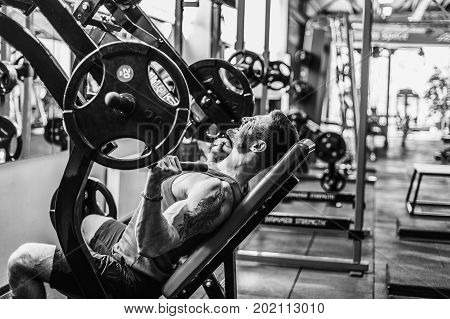 Sports guy doing exercise for the shoulders on the simulator in the gym. Brutal sports man. Bodybuilder on training in the gym. Health and fitness
