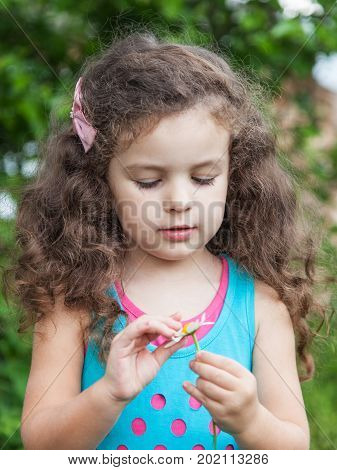 Girl with daisy in her hands Cute baby girl guesses on a camomile flower