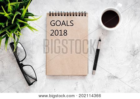 Words Goals for 2018 writting in notebook near glasses and cup of coffee on grey stone background top view mockup.