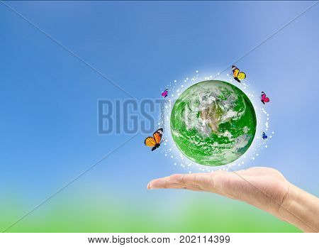 Earth Planet With Butterfly In Hand Against Green Blurred Background. Earth Day. Spring Holiday Conc