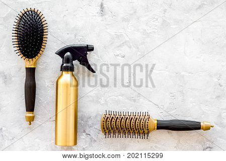 golden combs and spray for hairdresser work set on stone desk background top view mock-up