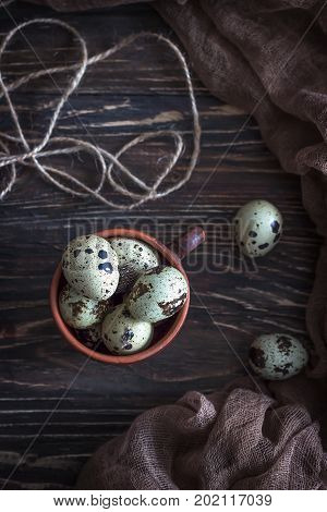Quail eggs on the rustic wooden background. Top view