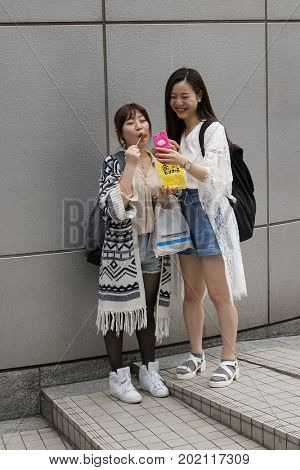 Tokyo, Japan -  May 12, 2017: Japanese girls making fun and a self portrait in the street of Tokyo