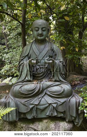 Tokyo, Japan -  May 12, 2017: Bhudda statue with Japanese coins in the garden of the Nezu museum