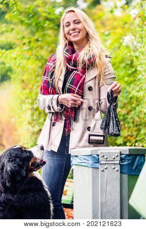 Woman is picking up dog poo putting it in dustbin keepint the nature clean