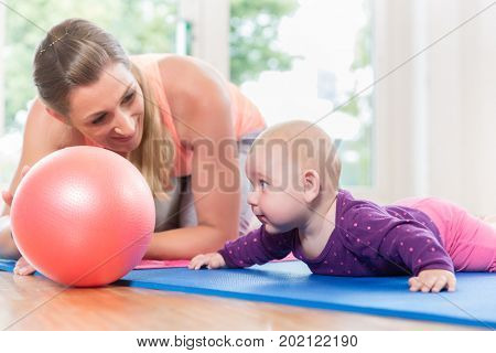 Mom and her baby practicing to crawl in mother and child course learning together
