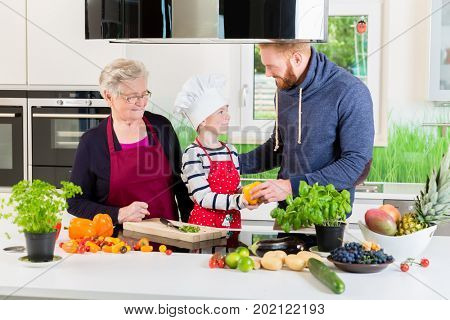 Dad, grandma and kid cooking together in kitchen with the whole family