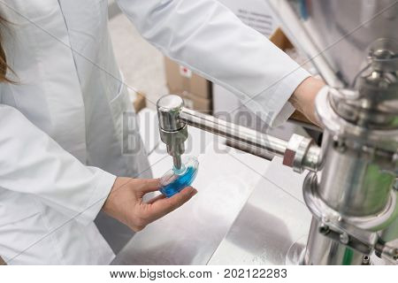 Side view close-up of the hand of a female technician filling a plastic container with liquid substance, for laboratory tests during quality control in a cosmetics factory