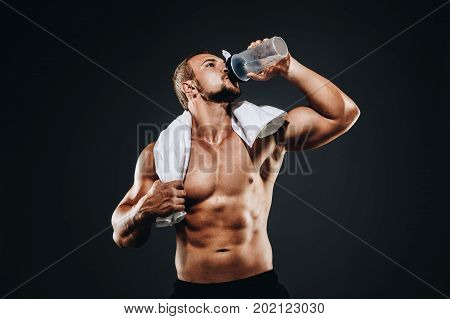 A Handsome Young Sportsman Standing Half Naked And Drink Water From A Shaker With A Towel In His Nec