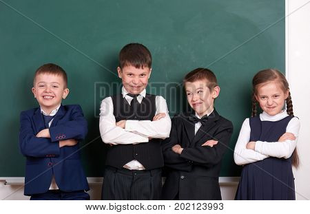 group pupil as a gang, posing near blank chalkboard background, grimacing and emotions, friendshp and education concept