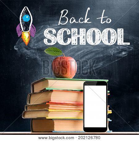 Back to School. Smartphone, books and fresh apple against blackboard