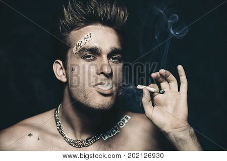 Antisocial behavior, bad habits. Portrait of a bad boy smoking cigarette. Rocker, punk.