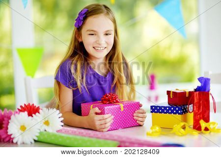 Cute Preteen Girl Wrapping Gifts In Colorful Wrapping Paper.