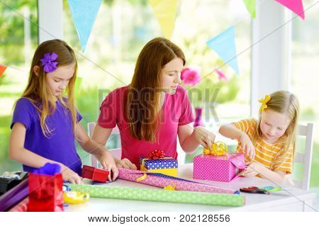 Two cute sisters and their young mother wrapping gifts in colorful wrapping paper. Family of three wrapping birthday presents. Family fun.