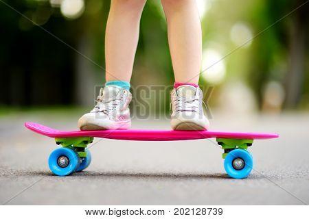 Closeup Of Skateboarder Legs. Kid Riding Skateboard Outdoor.