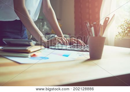 woman working laptop on wooden desk in office in morning light. The concept of modern work with advanced technology. vintage effect