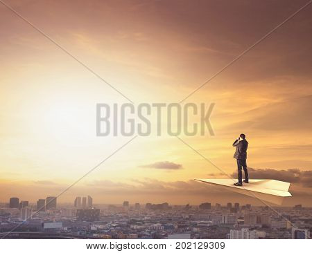 business man on paper plane spying by binocular to urban scene