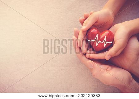 adult and child hands holding red heart with cardiogram health care love and family concept