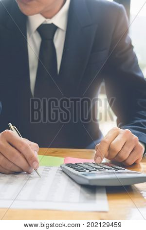 Business Man Using Calculator With Data Paper On Wooden Desk. Finance Concept.