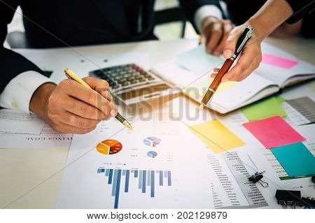 Close Up Of Business Man And Woman Hand Pointing At Business Document On Financial Paper During Disc