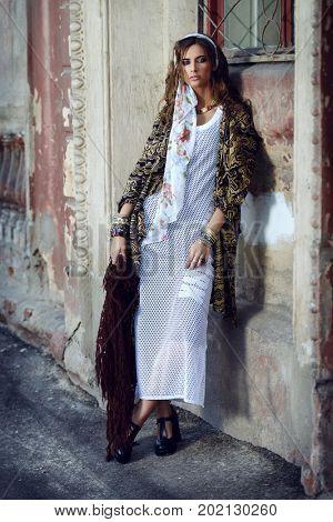 Female style. Feminine fashion model posing in boho style clothes on a street. Outdoor fashion.