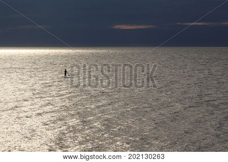 silhouette of woman - SUP surfer against the background of the oil platform under construction in the twilight