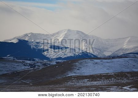 ice capped mountains and snow covered rolling foothills