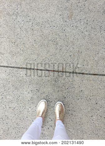 Aerial view girl in white jeans, white pants and gold studded shoes standing on the sidewalk with a crack in it